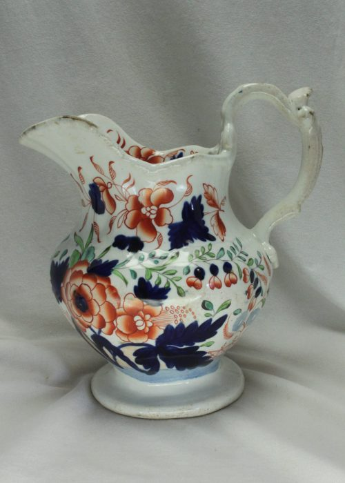 Hand coloured jug with ornate handle